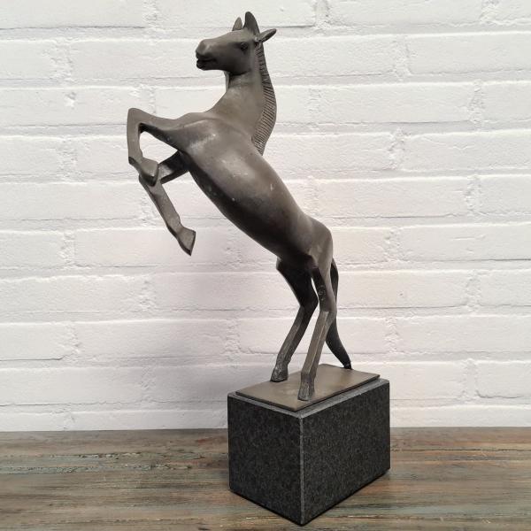 Gepatineerd stijgerend paard hardstenen voet. Hoogte 49 cm